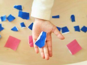 子どもがちぎった折り紙をもつ画像